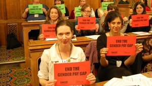 People in Parliament holding up signs reading End the gender pay gap