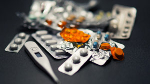 A pile of pills and a pregnancy test against a black background