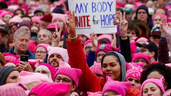 People protesting at the Womens March with a sign reading My body. Unite for hope