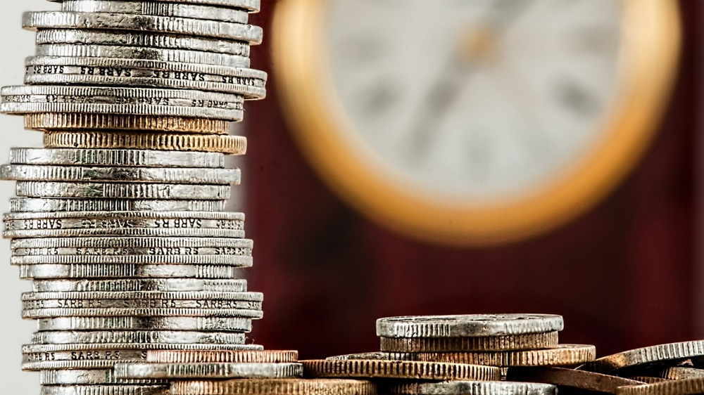 Stacked up coins, clock in background