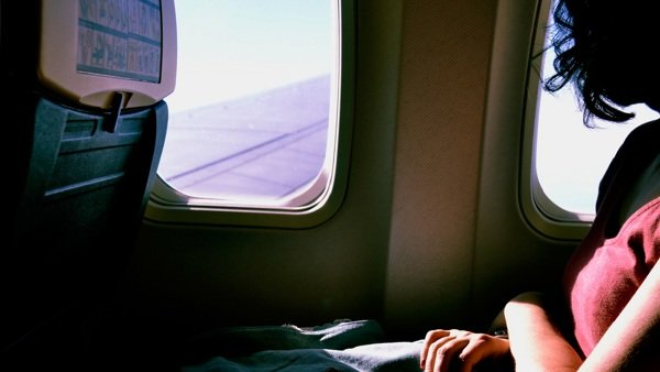 Woman sitting on plane looking out window