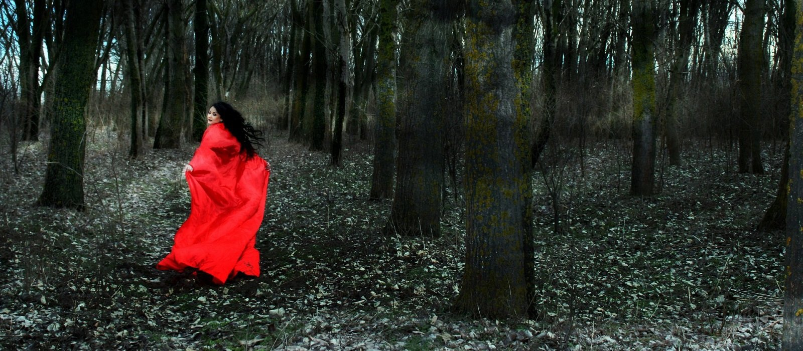 Woman in red cape running through forest