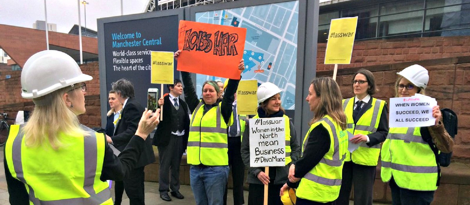 Women protesting in neon jackets and hard hats at a protest