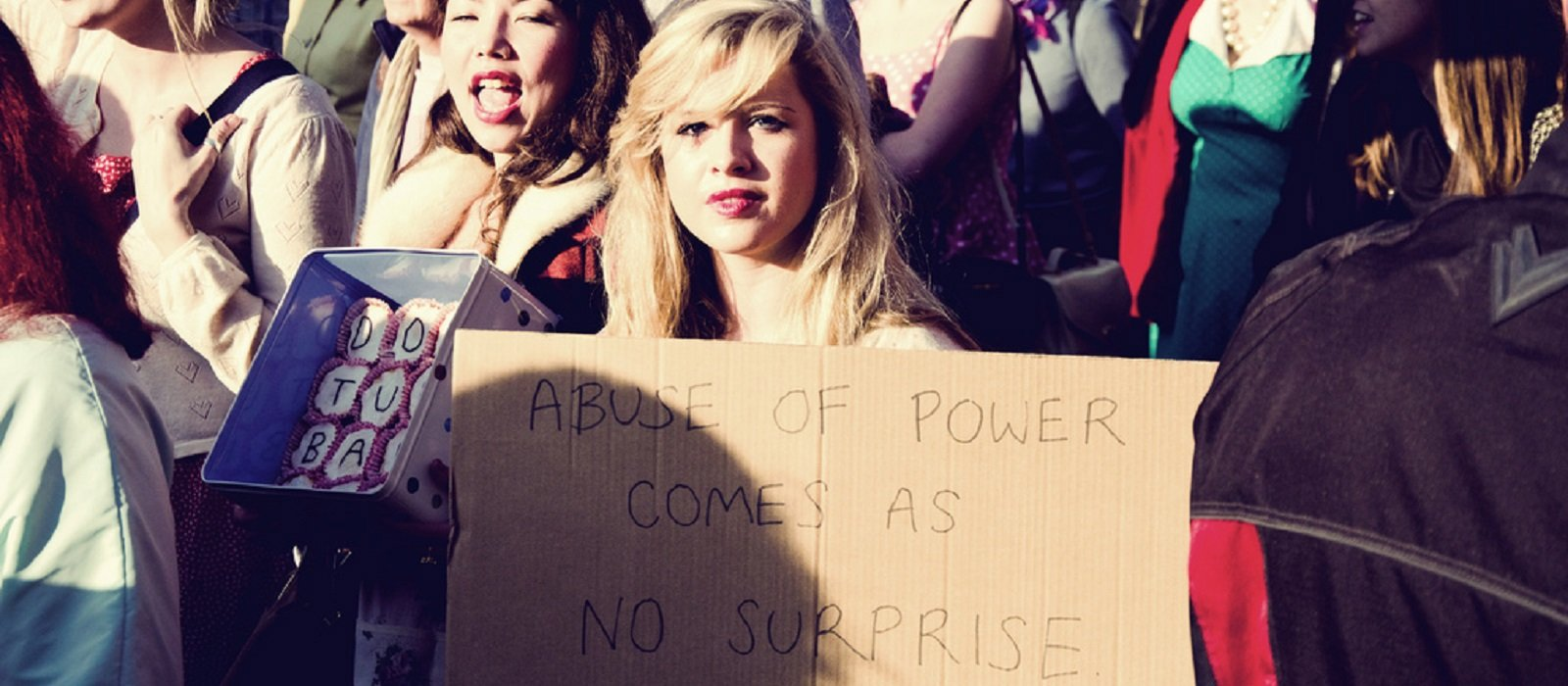 Woman holding sign that reads Abuse of power comes as no surprise