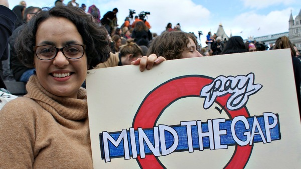 Woman holding sign that reads mind the pay gap